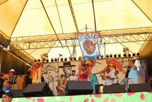 Foto de apresentação do Jaraguá Makungu, no detalhe cacau Segurando o estandarte do grupo
